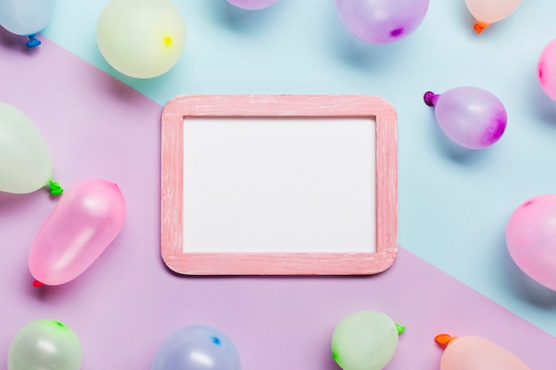 White blank frame decorated with balloons on blue and pink background Free Photo