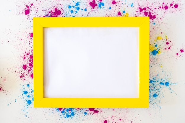 White blank frame with yellow border on holi color powder over white background Free Photo
