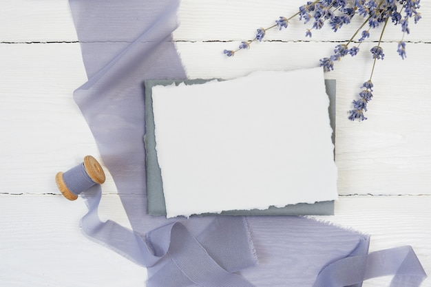 White blank greeting card ribbon on a background of blue fabric Premium Photo