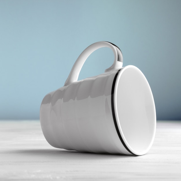 White blank mug lying on side on white wooden table and blue background Premium Photo