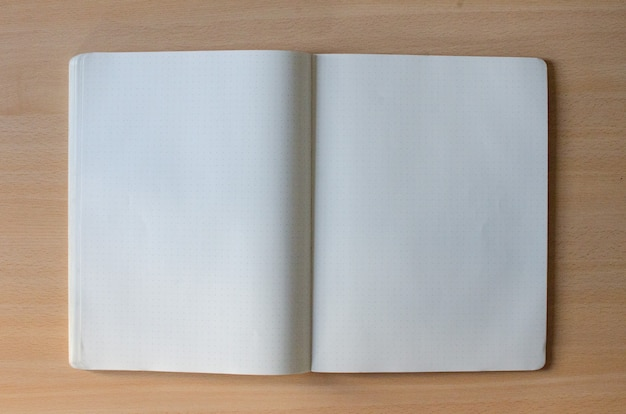 White blank opened copybook with a lot of space of text on a wooden background Free Photo