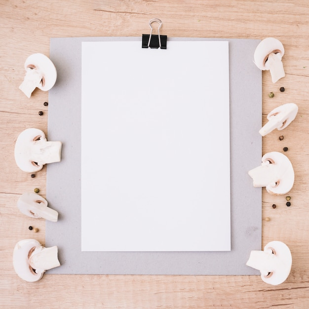 White blank paper attach on clipboard decorated with halved mushrooms and black pepper against wooden textured backdrop Free Photo