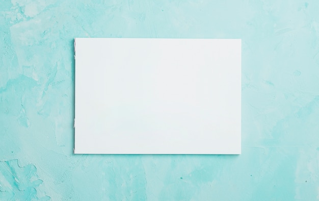 青い織り目加工の表面上の白い空白の紙のシート Premium写真