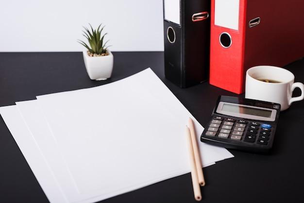 White blank papers; pencils; pot plant; paper files; coffee cup and calculator on black desk Free Photo