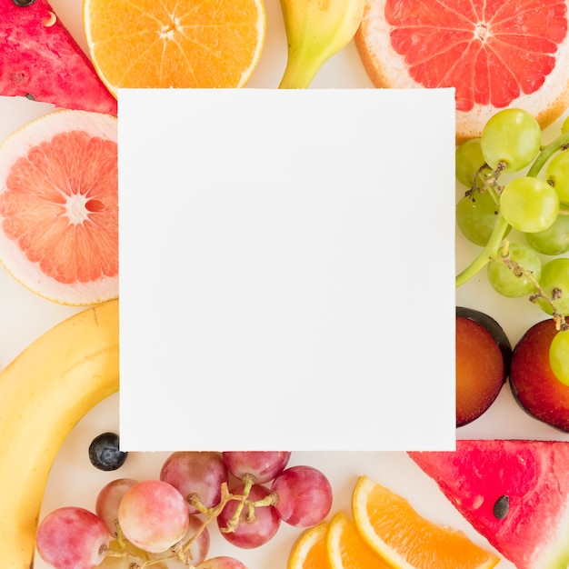 White blank placard over the colorful citrus fruits; grapes and watermelon Free Photo