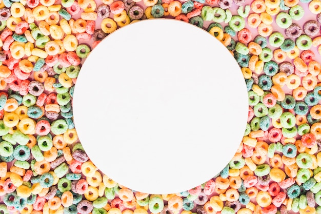 White blank round frame on the colorful cereal loop rings backdrop Free Photo