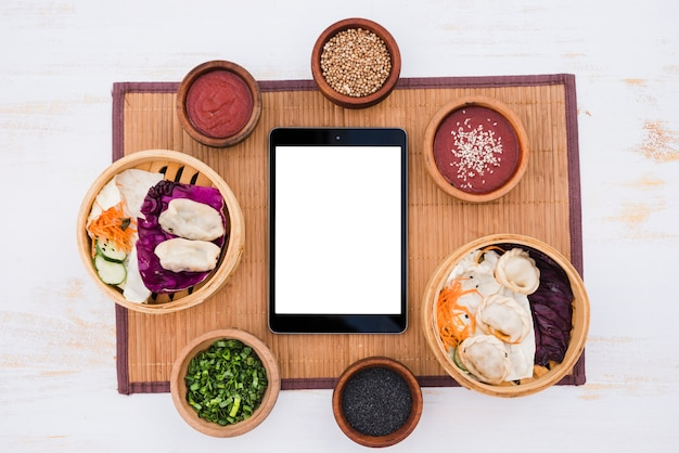 White blank screen digital tablet surround with sauce; chives and sesame seeds on placemat over texture backdrop Free Photo