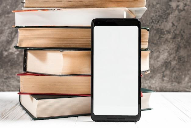 White blank screen display mobile phone in front of book stacked on table Free Photo