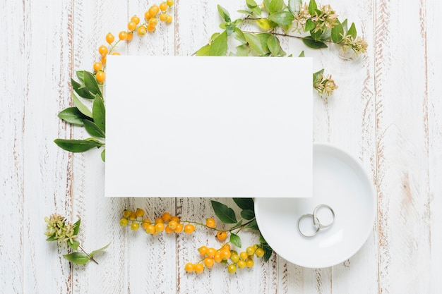 White blank wedding card with flowers; yellow berries and wedding rings on wooden backdrop Free Photo