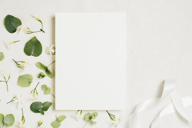 White blank wedding card with jasminum auriculatum flowers and ribbon on white backdrop Free Photo