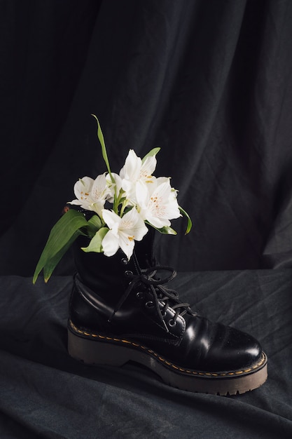 White blooms in dark leather boot Free Photo
