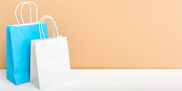 화이트 블루 크래프트 종이 봉지. 쇼핑 이랑 가방 복사 공간 흰색 테이블 베이지 색 밝은 배경에 종이 패키지. 프리미엄 사진