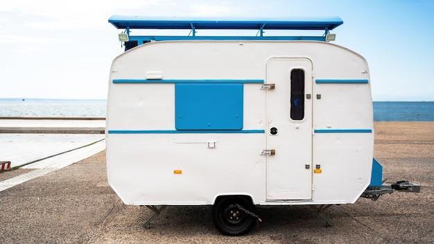 Rimorchio di viaggio bianco e blu con il mare sullo sfondo a salonicco, grecia Foto Gratuite