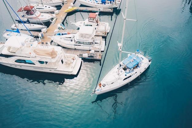 La barca bianca che lascia i porticcioli del porticciolo naviga sull'acqua Foto Gratuite