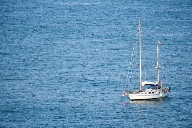 Barca a vela bianca nel mare tranquillo durante il giorno Foto Gratuite