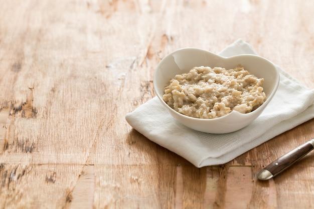 White bowl of oats porridge. healthy oatmeal breakfast Premium Photo