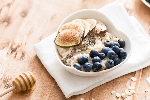 White bowl of oats porridge with figs, blueberries and chia seeds. Premium Photo
