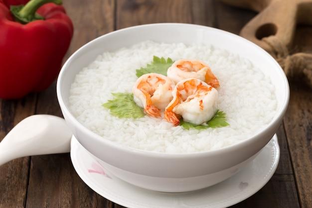 White bowl of shrimp porridge, thai rice soup with shrimp (khao tom koong) on wood Premium Photo