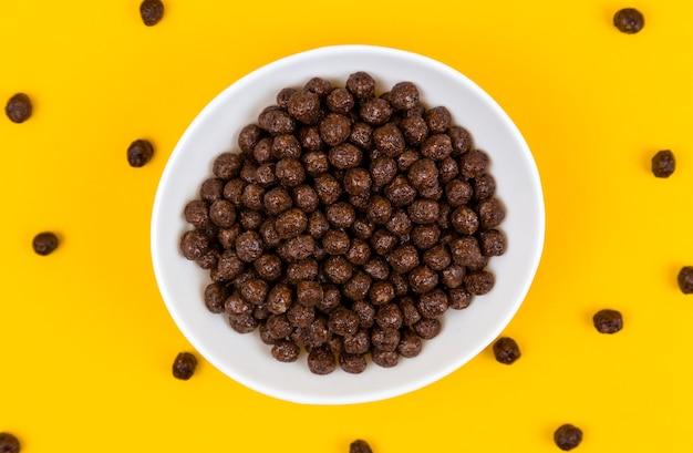 Белая миска с шоколадными кукурузными хлопьями и молоком на желтом Premium Фотографии