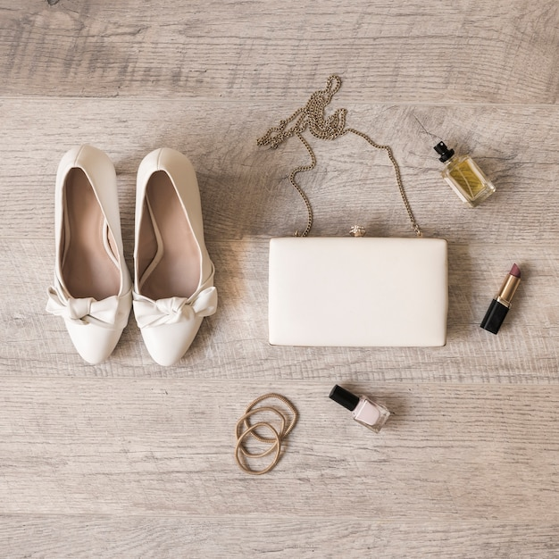 White bride shoes; perfume; lipstick; hairbands; clutch and hair bands on wooden background Free Photo