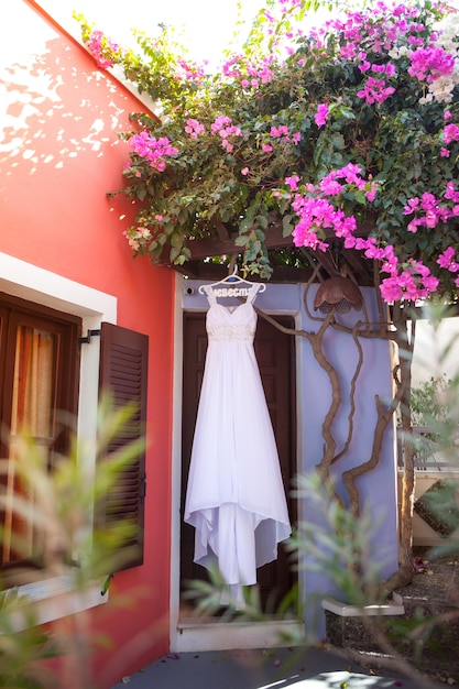 White bridesmaid dress hanging on hangers with an inscription in russian bride under the blossoming bougainvillea in a quiet courtyard on santorini, greece Premium Photo