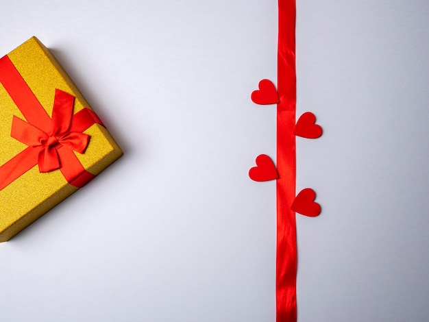 On a white bright background lies a long red ribbon surrounded by four hearts and next to a yellow gift with a red ribbon Premium Photo