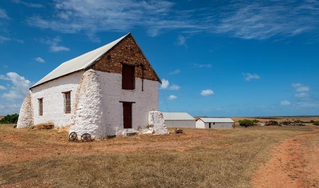 曇り空の下で農村地域の農場のフィールドにある白い建物 無料写真