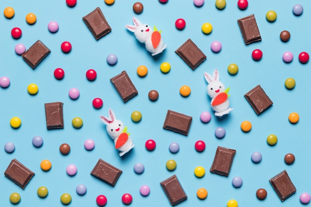 White bunnies; gem candies and chocolate pieces on blue backdrop Free Photo