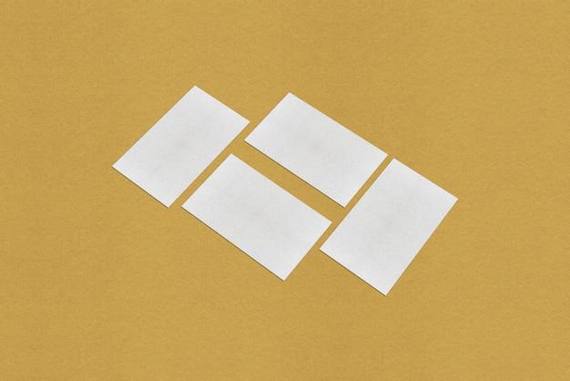White business card mockup, white business card on golden background Premium Photo