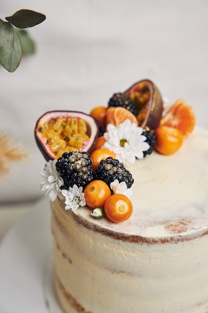 植物の横にベリーとパッションフルーツの白いケーキ 無料写真
