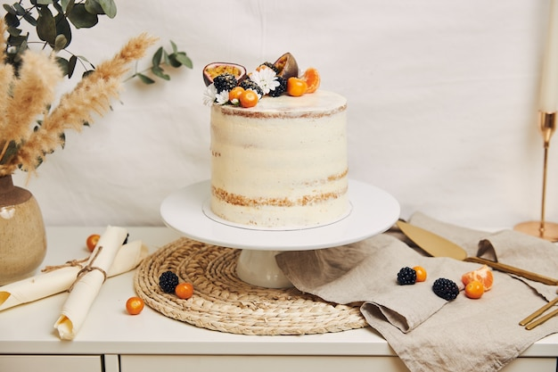 白い後ろの植物の横にベリーとパッションフルーツの白いケーキ 無料写真