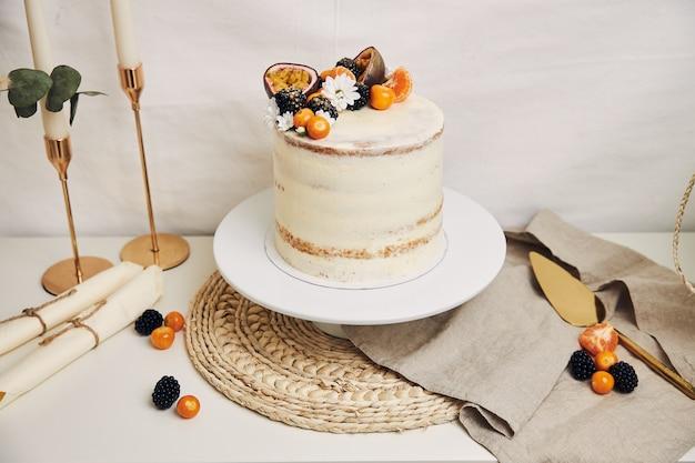 白い背景の後ろに植物とベリーとパッションフルーツと白いケーキ 無料写真