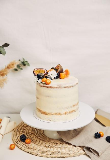 Torta bianca con frutti di bosco e frutti della passione con piante Foto Gratuite