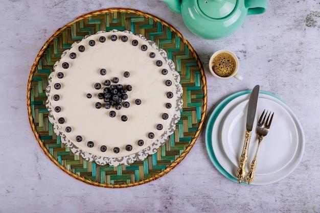 トップ、コーヒー、プレートに新鮮なブルーベリーの白いケーキ。 Premium写真