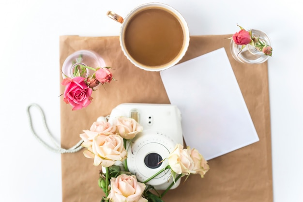 White camera on the desktop among the flowers next to a cup of coffee Premium Photo