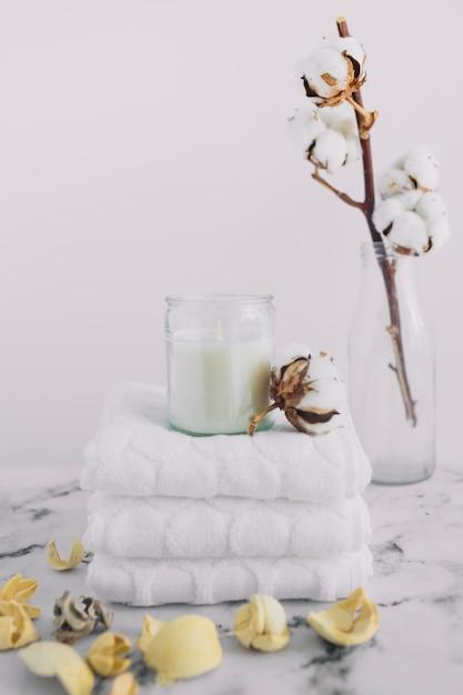 Candela bianca nel candelabro sopra tovaglioli bianchi accatastati vicino baccelli secchi e ramoscello di cotone in bottiglia Foto Gratuite