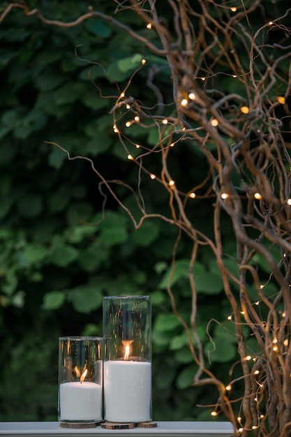 White Candles In Tall Vases Stand Under Dry Branches With Fires