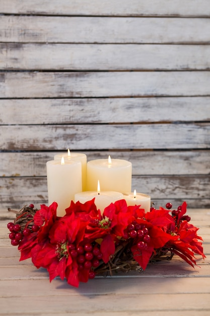 White candles lit with red flowers Free Photo