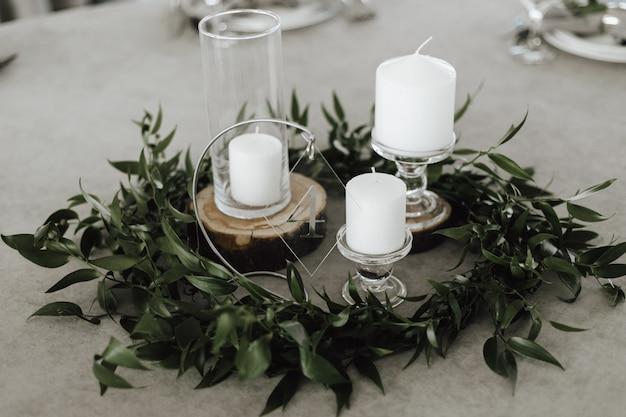 緑の葉に囲まれた灰色の背景にガラスの燭台に白いキャンドル 無料写真
