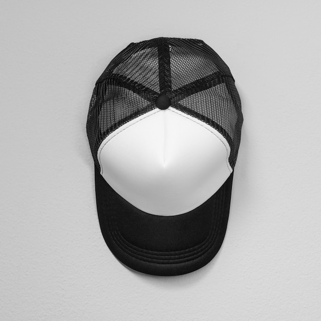 White caps with black nets on cement background. top view angle of baseball cap. Premium Photo