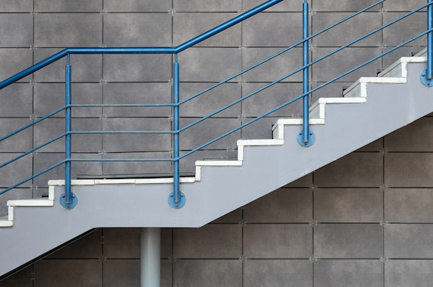White cement stairs with blue steel railing on gray tiled wall background Premium Photo