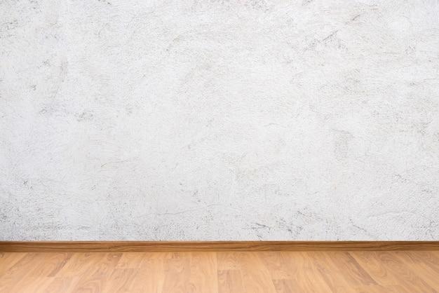 白いセメントの壁の質感と茶色の木の床 Premium写真