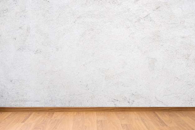 White cement wall texture and brown wooden floor Premium Photo