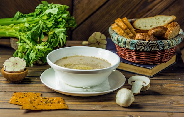 A white ceramic bowl of mushroom soup served with garlic gloves Free Photo