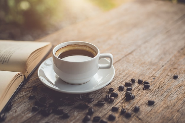 White ceramic coffee cup of black hot americano on wooden table Premium Photo