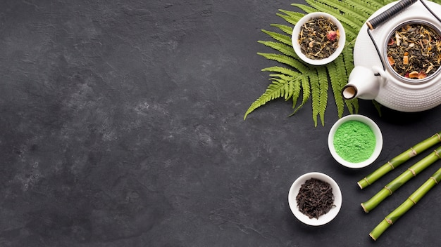White ceramic teapot and dry tea herb with matcha tea powder on black backdrop Premium Photo