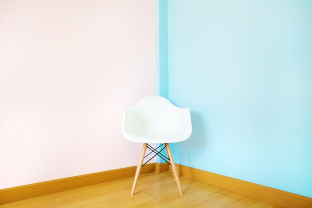 White chair in living room on pastel wall Premium Photo