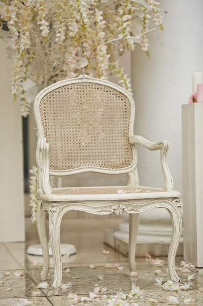White Chair Stands On White Petals Outside Free Photo