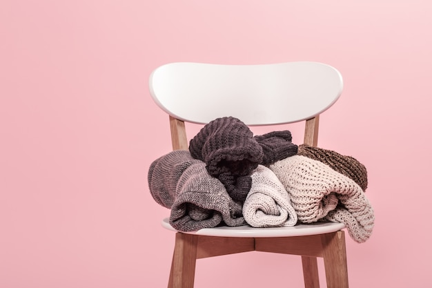 White chair with a stack of knitted sweaters on a pink wall Free Photo