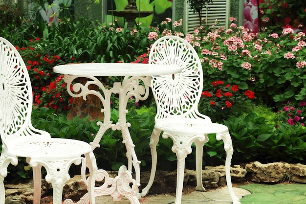 White chairs and round table in the flowers garden. Premium Photo